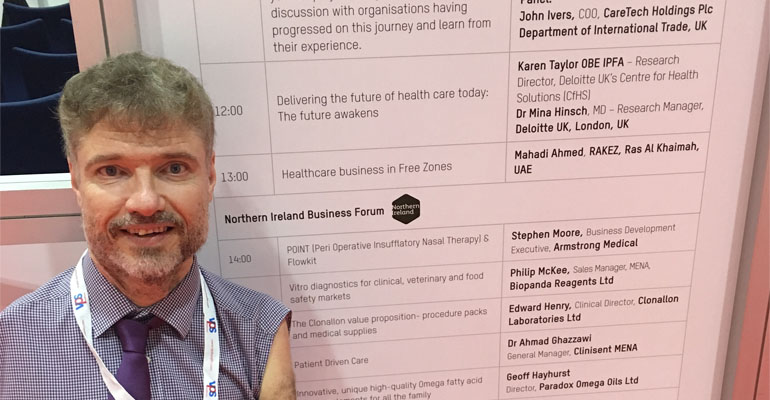 Mike Adams standing next to the schedule board at the Arab Health Conference.