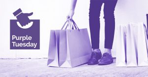 Woman carrying a number of shopping bags, and the Purple Tuesday logo.